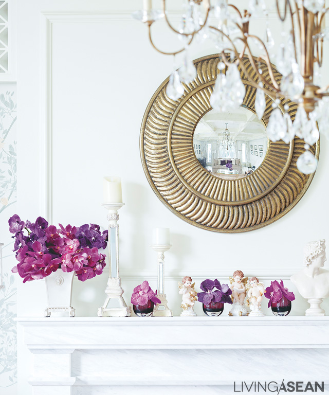 The parlor's white wall brings out the gold of decorative wall mirrors and hanging lamps. Orchids are arranged in small bouquets.