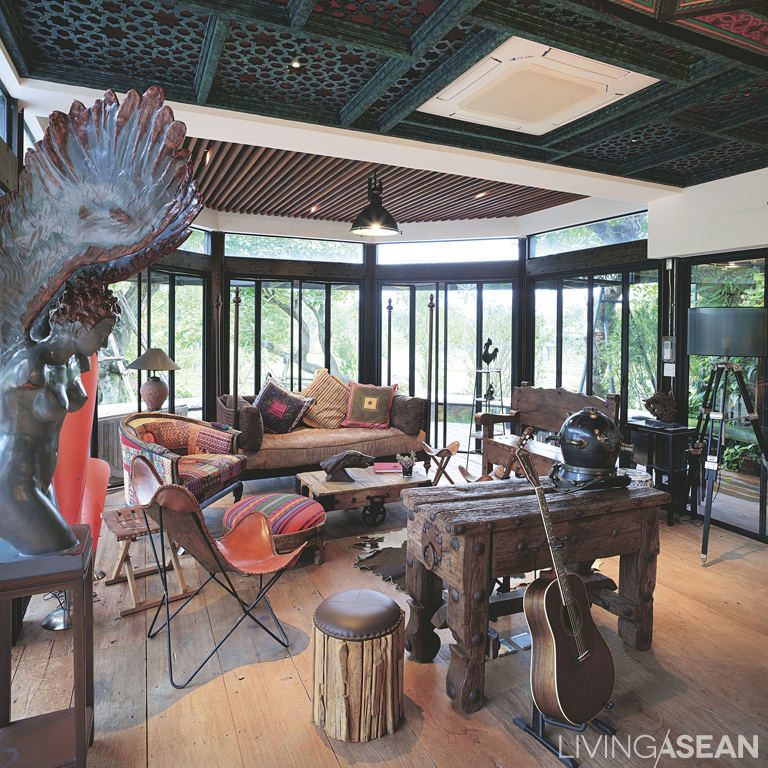 """""""This room is affectionately called """"The aquarium,"""" although people live in it. Spectacular panoramic views can be seen from here. It is a glass-wrapped living room with a typical Safari feel to it. Furniture pieces strike the right balance between old wood, leather, and vernacular style upholstery."""
