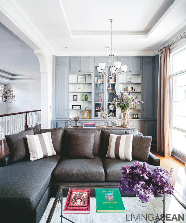 """The """"living room"""" corner on the second floor has grey shelves behind it. The strong brown of the sofa and gently patterned throw pillows give warmth to the room and make it an attractive place to be."""