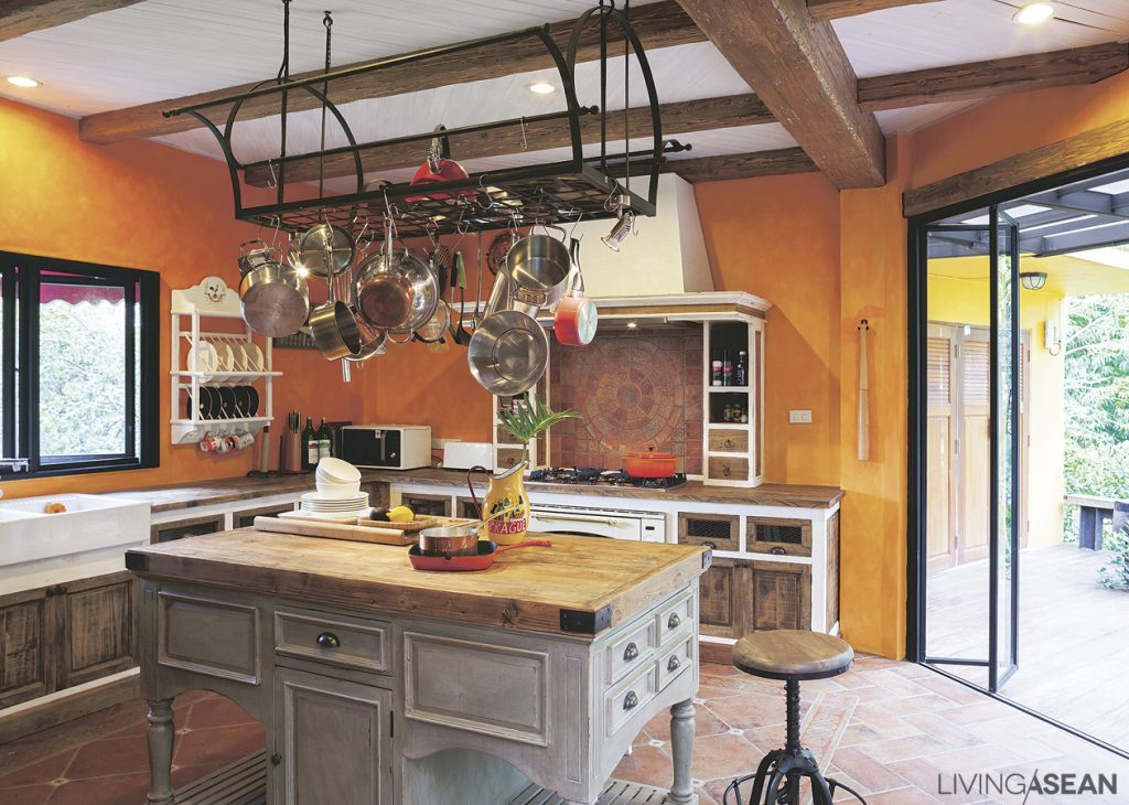 The kitchen has a Country Rustic feel to it. Orange walls characteristic of Fresco architecture add the charm of a Tuscan village to the atmosphere. The kitchen island is crafted of pinewood in lighter shades to bring out the superb natural wood grain that whispers soft Rustic appeal.