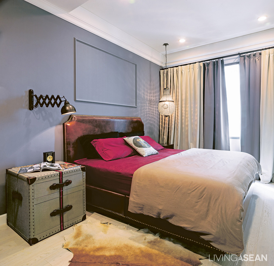 The bedroom is simple but striking. The pigeon-gray wall contrasts with the crimson bed sheet. Gimmicks lie in details, such as using an industrial lamp instead of an ordinary reading light, while a fancy crystal chandelier-like lamp is hanging on the far side.