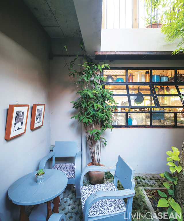 A coffee corner sits on the patio decorated with old pieces of furniture. Long roof overhangs and the crisp cool canopy of tall trees combine to make the area very comfy.