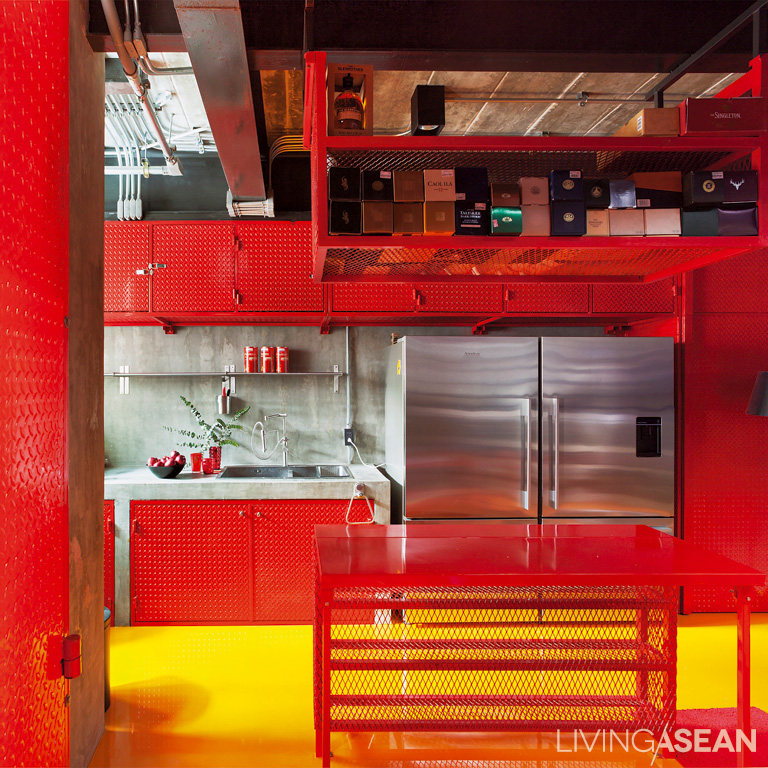 The red kitchen combines a striking color with a raw, industrial style. The kitchen counter is made of polished concrete. Inside is a built-in checker plate closet.