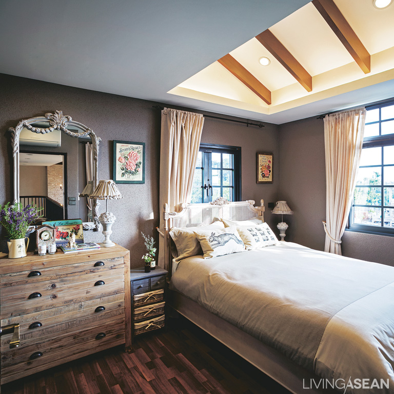 The master bedroom with charming country-style furnishings: Wooden beams are set above the bed for decorative effect. Recessed and indirect lighting provides a soft, relaxing illumination.