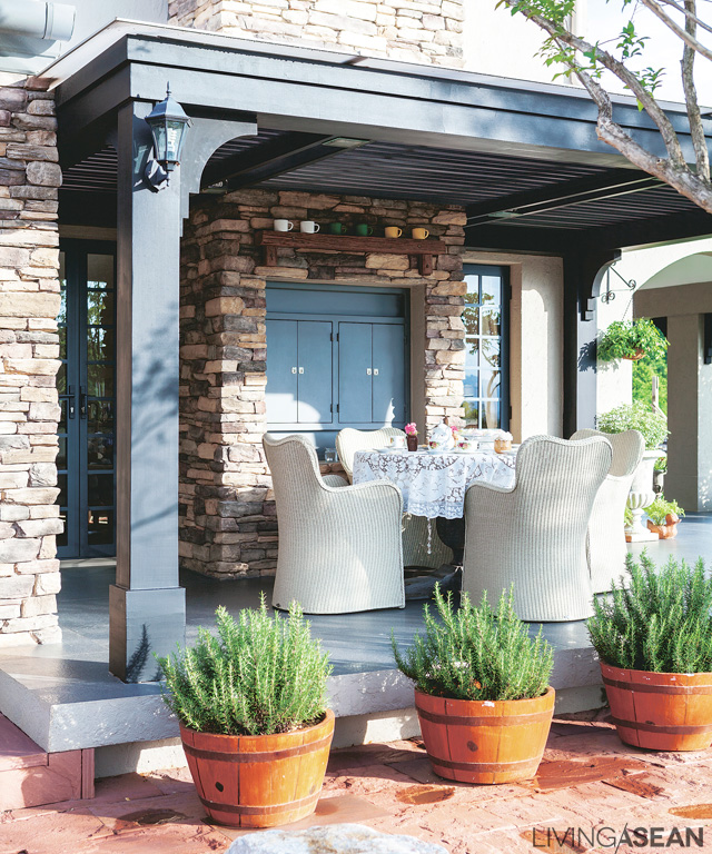The deck on the far side of the house is under an extended roof. Table and chairs are set out for easy dining or a small family party.