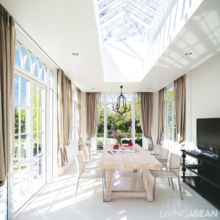 A roof of clear glass lets natural light into the mid-garden gazebo. Surrounding aluminum-framed glass walls connect a view of the garden outside.