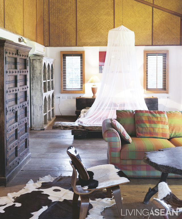 """The bedroom inside """"Tarzan's house"""" showcases antique Spanish-style cabinetry from Phoenix, a Chiangmai furniture store. To give it a vernacular touch, the walls and ceilings are made of woven bamboo panels mixed with OSB boards."""