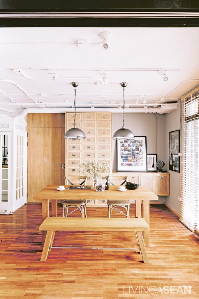 Different shades of teakwood add dimensional depth. Silver lamps draw attention to the pipe system on the ceiling.