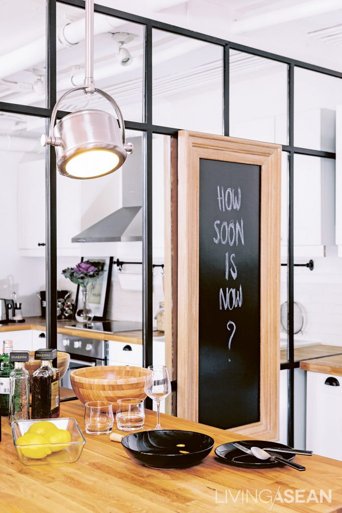 A metal-framed mirror wall creates an illusion of a larger kitchen.