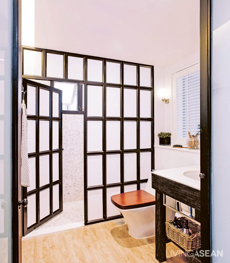 Oat replaced the old bathtub with a shower, separating dry and wet bathroom areas with a black-framed metal partition. The wood tile floor here brings a warmer feeling and a connection with other rooms.