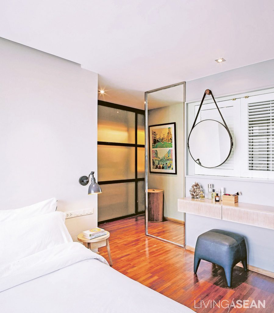 The clean and orderly bedroom connects to a dressing room. The black metal doorframes go well with the other parts of the home. Large glass pane along the corridor makes the space look wider and more open.