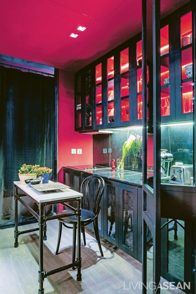 The pantry is striking. With its red wall and ceiling and multicolor drapes, the dark metal Arabian-style partition setting it off from the rest of the home.