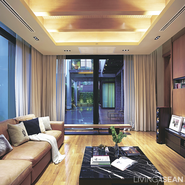 The upscale living room has only a few pieces of furniture. The coffee table has a hidden drawer for orderly storage of remote controls and other devices.
