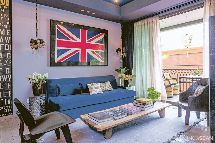 """Dark colors alternate with paler ones, giving dimension to the """"living room."""" The light gray wall is adorned with framed pictures. The teakwood floor is polished to a lighter shade, contrasting with the dark ceiling, and opens out onto the balcony, with its set of wicker chairs."""