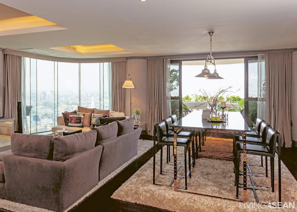 The dining area next to the living area is a relaxing place to sit and look at the river through the panoramic curved glass. The plush gray carpet adds a sweet touch to soften any rigidity in the look of the table and dining area.