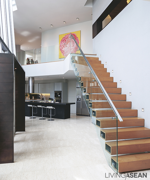 A staircase runs along the wall of the entryway. The high ceiling creates a relaxing visual effect.
