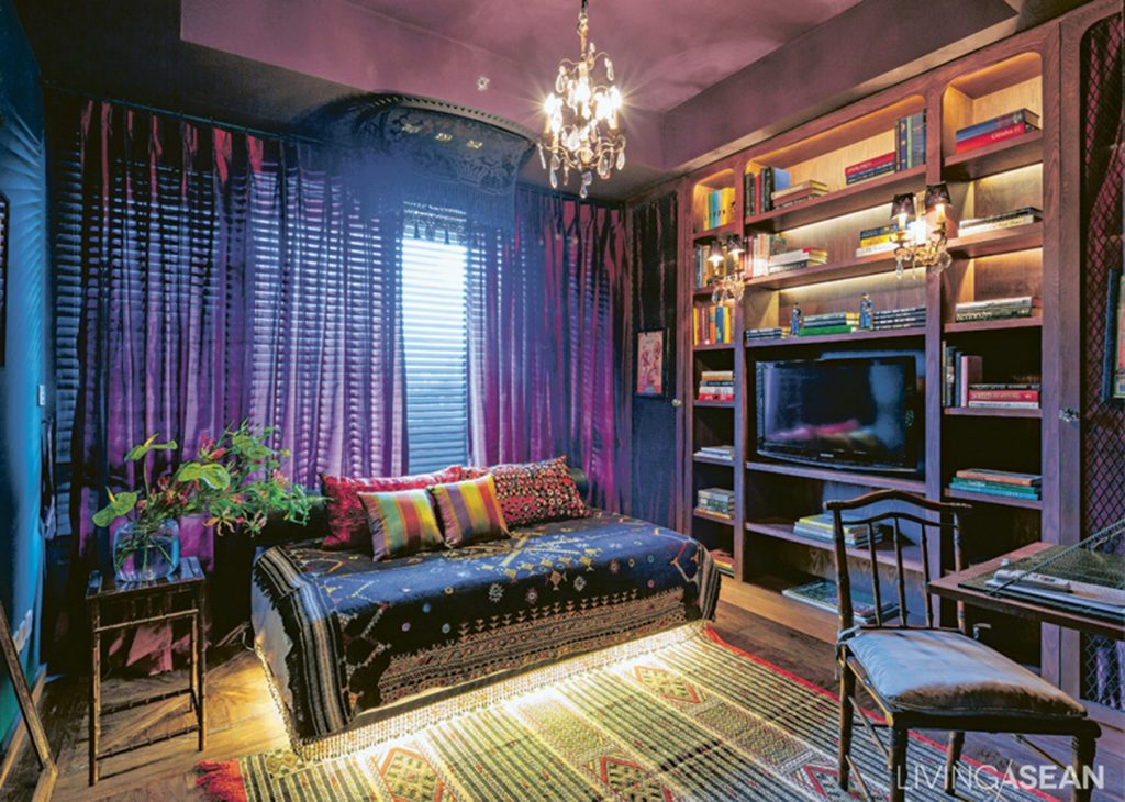 The room is vibrant with a strong artistry at work. The TV sits on a mock up fireplace. LED lights give a romantic mood during the nighttime.