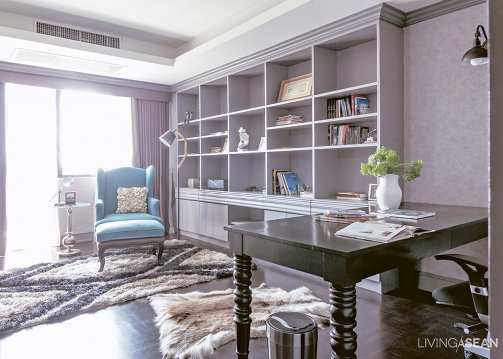 The workroom is done simply, in dark grays, the mood broken up and made relaxing with a brightly-colored armchair and soft carpet.