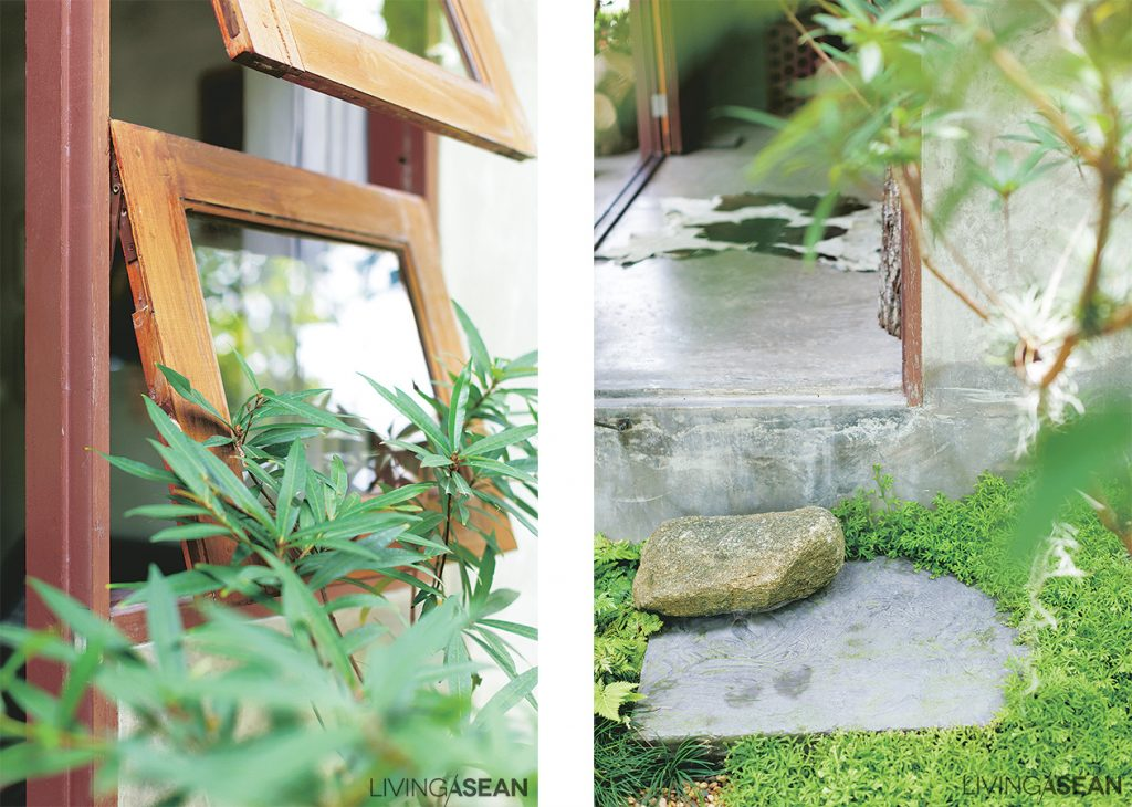 Big rocks are used to make steps that connect the front porch to the garden below. Together they add a country rustic feel to the lush green setting.