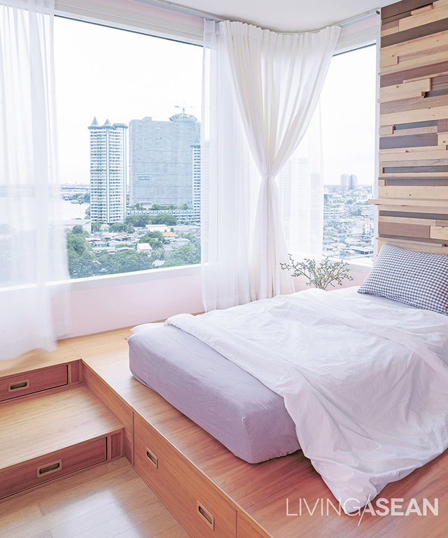 Mother and daughter share this bedroom, with mattress set at a higher level. Storage drawers are built in between levels. The wall surface has a novel look: wood veneer of varying colors and sizes, some pieces extending out far enough for small items to be placed there.