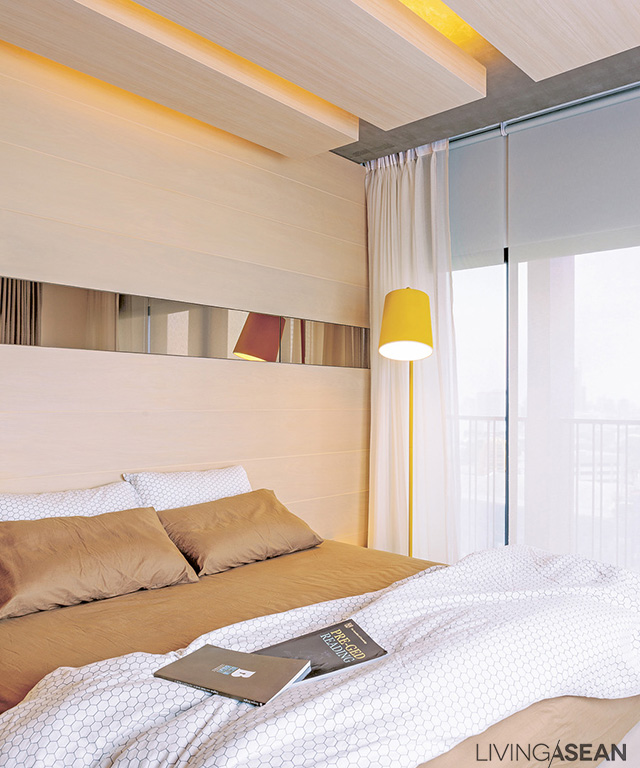 The shared bedroom is orderly and simple. Still, there is interesting detail: lighting works are hidden inside the lowered ceiling panels. The gaps in the ceiling are echoed with the long mirror set in the wood wall paneling.