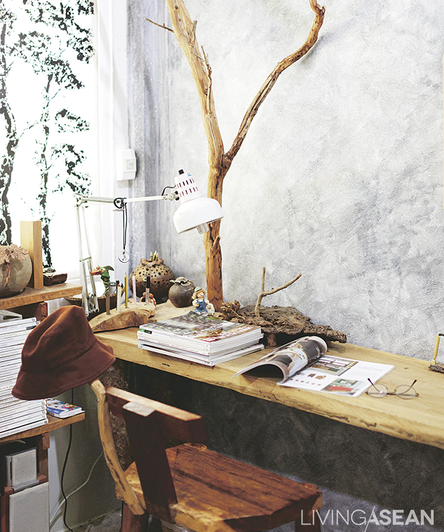 Twigs anchored against the rustic looking wall and furniture serve as racks for hanging hats and tchotchkes from a lifetime of carpentry. House and garden publications that are his pastime are kept here.