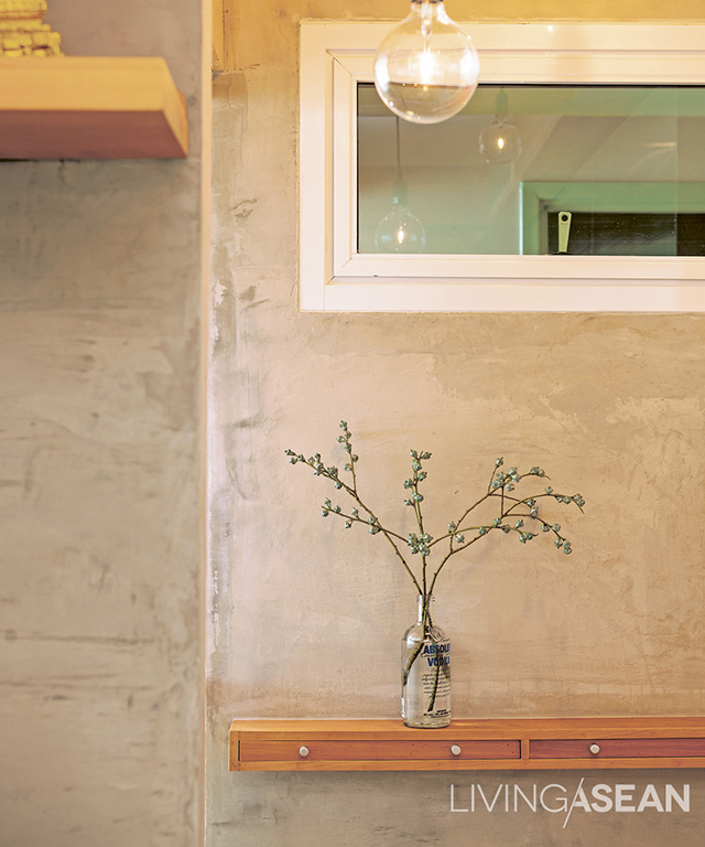 The unfinished concrete wall adds a charming and visually simple touch with a single plant set on a 20-centimeter-deep shelf of drawers with tiny handles. This can be used to place keys or other small items before going into the bedroom.