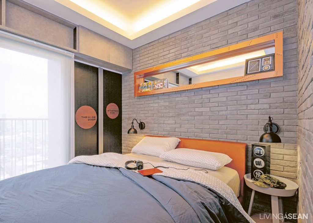 Bu's bedroom offers a bit of underground chic with its stylized gray brick wall, reducing any seriousness implied by the brown leather bed upholstery. The shelf's inner mirrors add an interesting dimension to the room.