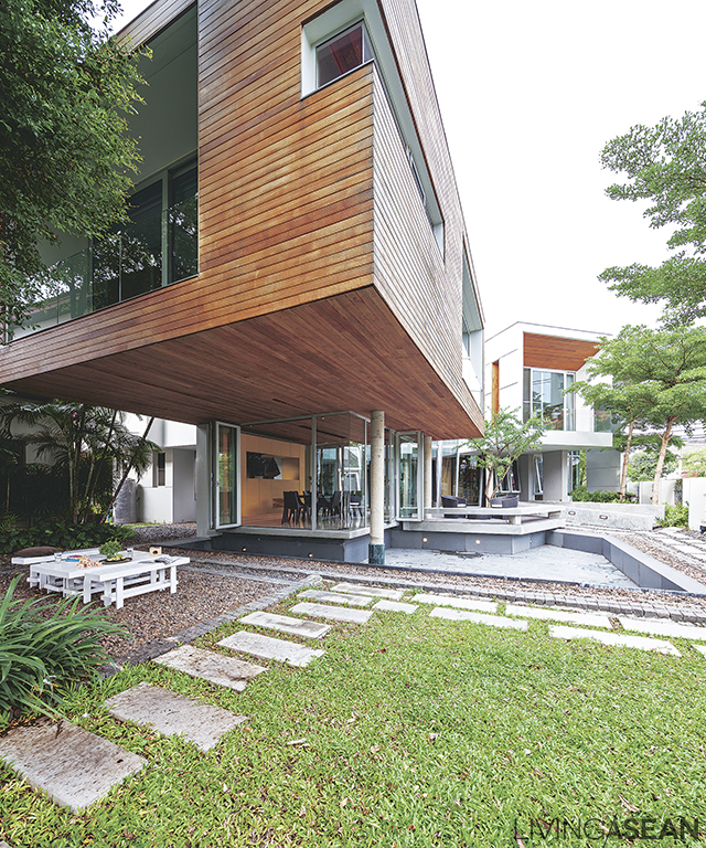 The house extends out above the outdoor family area while requiring only minimal support posts.