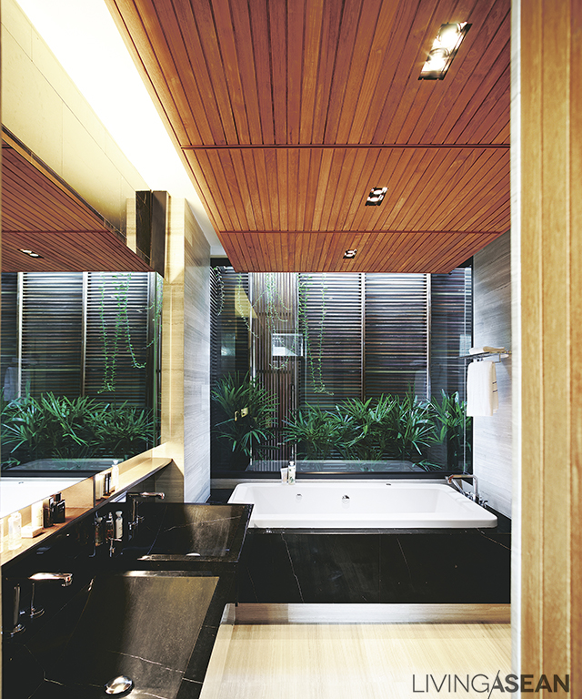 Dimmed light in the master bathroom builds a warm mood. Décor is mainly of granite and wood. An opening is provided for ventilation and natural light.
