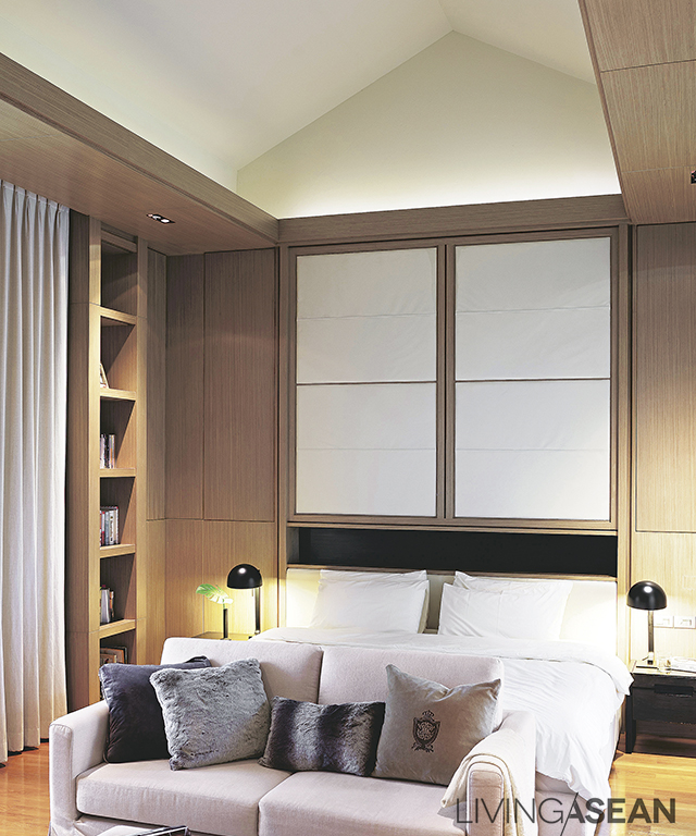A high-ceilinged bedroom comes in soft-colored décor. Hidden ceiling lights add dimension, creating an illusion of an even taller space.
