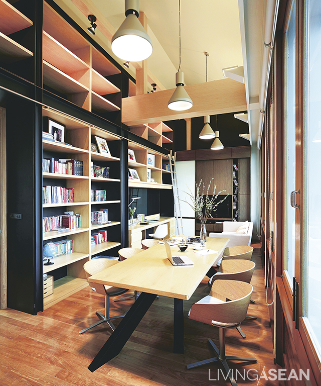 """Working corner and reading room on the top floor. The true surface of the wood beams is exposed, for the hint of a loft environment. One wall has metal """"C' Shape frames attached so it can be used for bookshelves."""