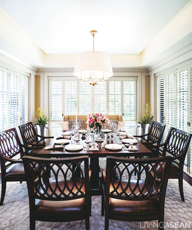 The dining room is ringed by glass to let in natural light during the day. The dark furniture color reinforces a warm, welcoming atmosphere.