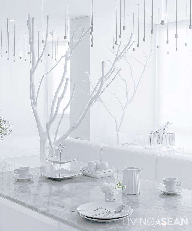 The dining table is topped with white marble, which is easy to clean. Decorative branches painted white give the sense of sitting under a tree.