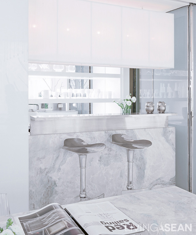 A mix of modern and oriental styles: The counter's marble surface matches the dining table. Hanging lamps are tied to a white steel frame.