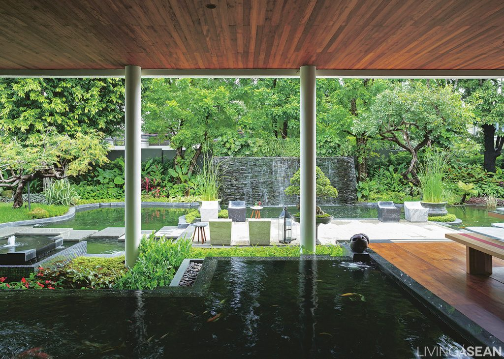 From the inside looking out, colorful varieties of plants abound. At the far end a beautiful waterfall fills the garden ambience with soothing sounds. In the foreground are two separate fishponds.