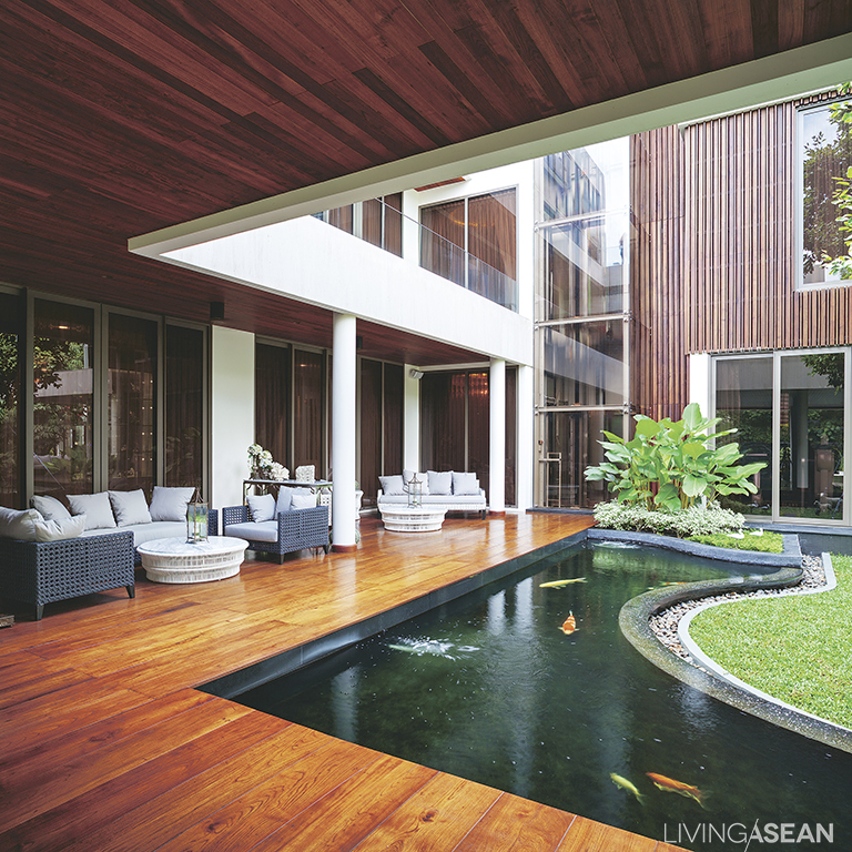 Wooden decking affords plenty of space for deck furniture made for socializing and admiring the scenery. Parts of the wood deck juts out over the carp pond.