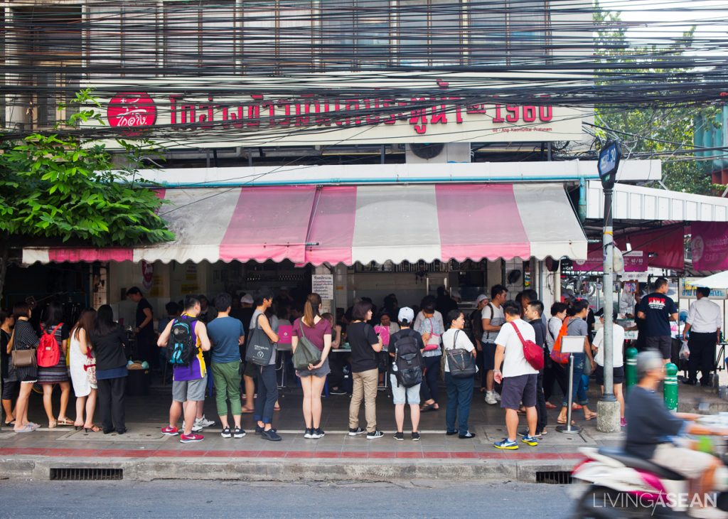 Customers queue up in front of a well-known chicken rice restaurant in Bangkok.