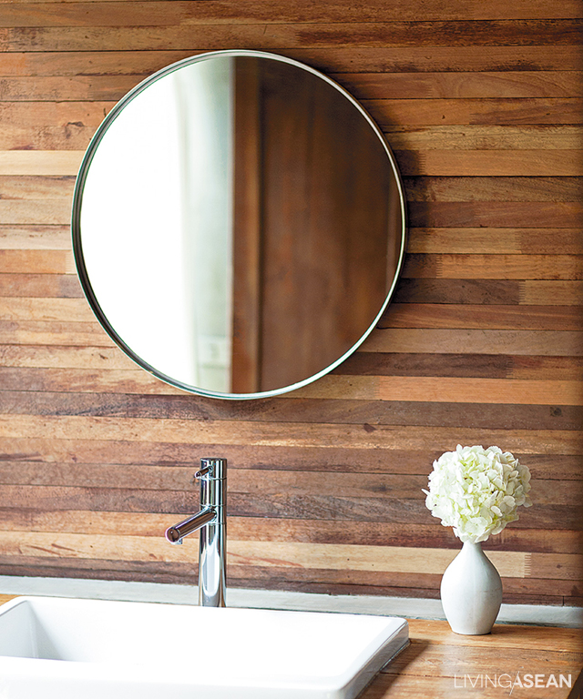 Timber makes up the wood paneling wall in the bathroom opposite the bedroom.