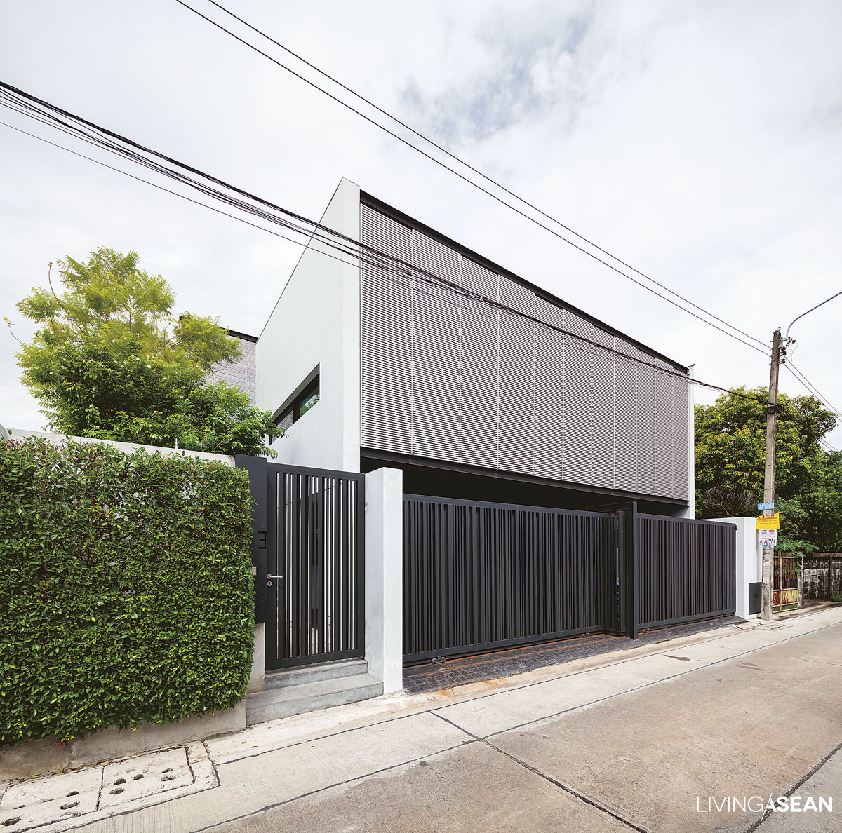 Tall aluminum latticework that makes the front façade protects the west-facing home from harsh sunlight. It provides a buffer against solar heat gain building up in the interior. On the street, black iron lattice fencing promotes natural air circulation and doubles as a privacy screen.