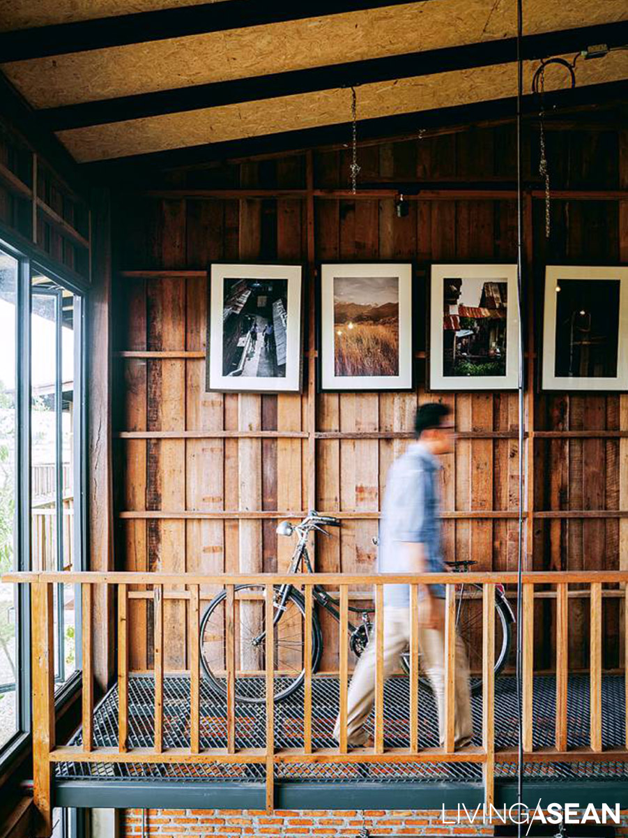 The small mezzanine, where we see a post-World War II vintage bicycle, is traversed by a steel walkway. Photos on the wall give the air of a private gallery.