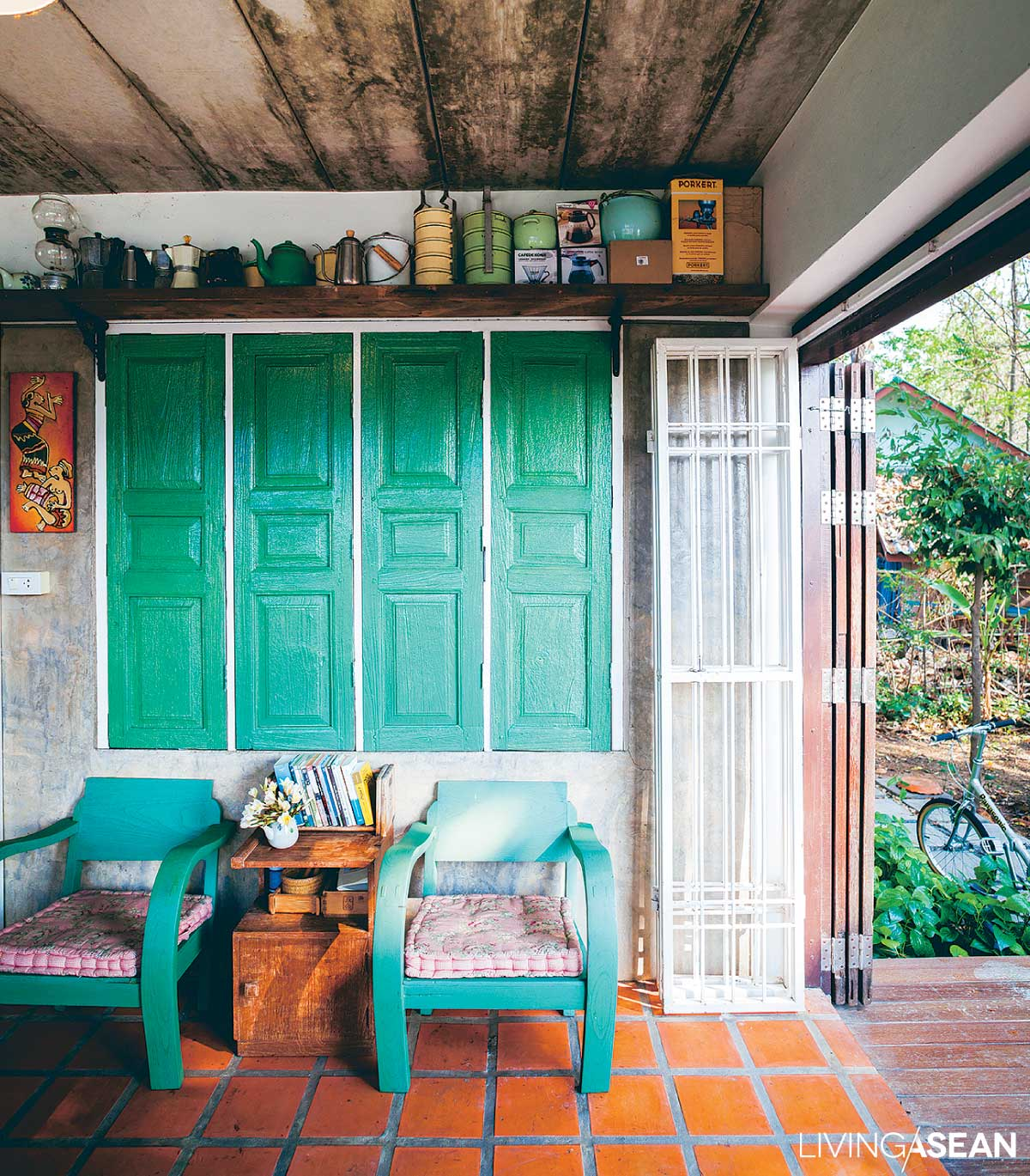 "The kitchen wall has painted green shutters, ""tank-shaped"" chairs, and a simple shelf above the door"