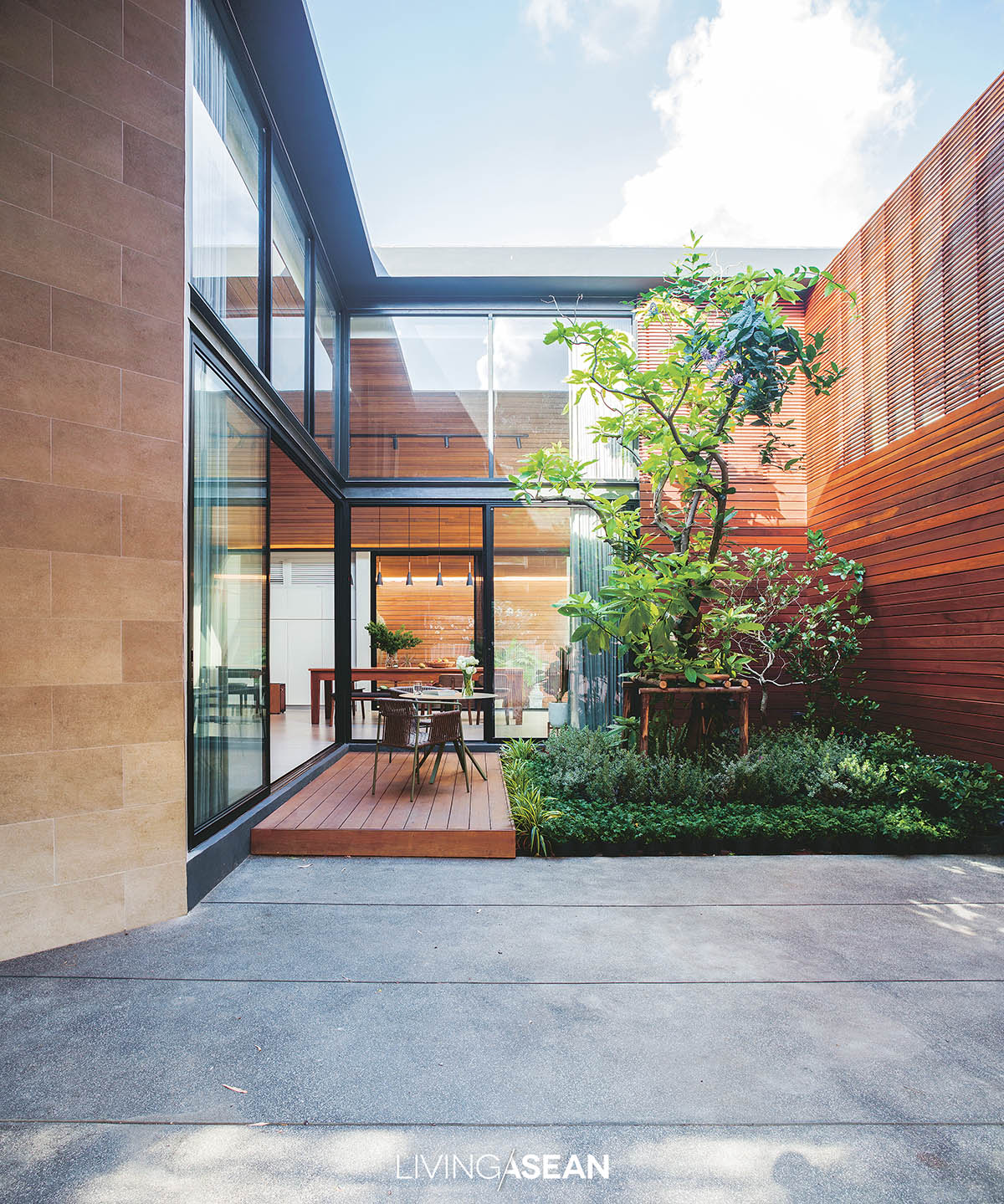 Beyond the carport, a courtyard lies mostly enclosed by glass walls that let natural light stream into the house's interior. At the center, a thriving lettuce tree (Pisonia grandis R. Br.) adds a decorative touch to the home.