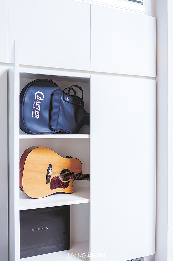 Built-in storage shelves provide a creative solution to dress up a blank wall. Each flat length of wood has enough room for a musical instrument and every conceivable gadget.