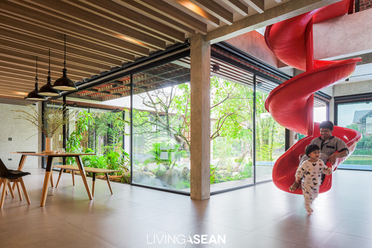 A red slide offers a fun way to enter to the living room, while the open floor plan gives the impression of more space and great reasons to float the furniture.